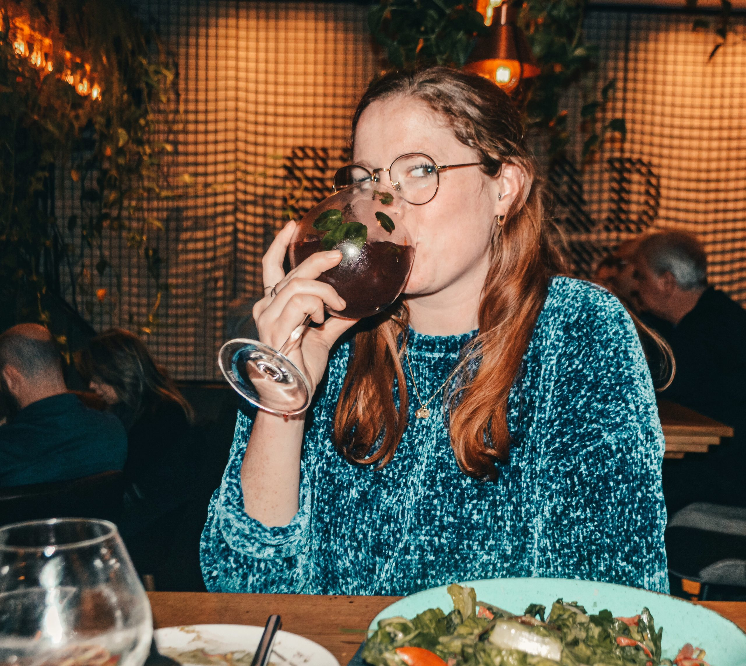 Girl drinking a large glass of sangria in a blue sweater at a vegan bar.