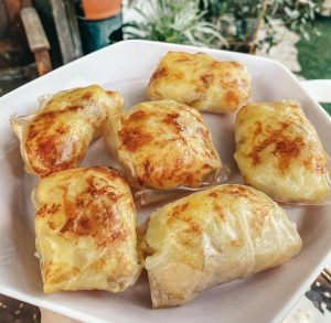 Crispy rice paper stuffed with potatoes and cheese on a pink plate.
