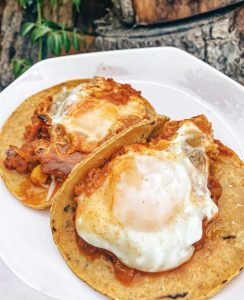 Two corn tortillas with red sauce and poached eggs.